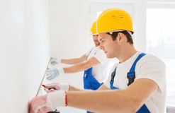 Group of builders with measuring tape indoors Royalty Free Stock Photo