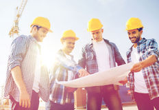 Group of builders with tablet pc and blueprint. Business, building, teamwork and people concept - group of smiling builders in hardhats with blueprint outdoors stock photography