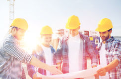 Group of builders with tablet pc and blueprint. Business, building, teamwork and people concept - group of smiling builders in hardhats with blueprint outdoors royalty free stock image