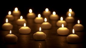 Group of burning candles at a black background Stock Photos