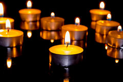 Group of burning candles on  black background. Royalty Free Stock Photos