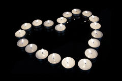 Group of burning candles forming a heart  on black isolated background. Royalty Free Stock Photo