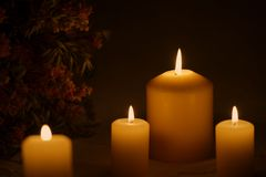Group of burning candles wit flowers. Four burning candles of different sizes in darkness with a bouquet of flowers in the background on a festive embroidered Stock Images