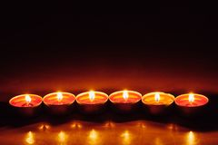 Group of burning red tealight candles Stock Photos