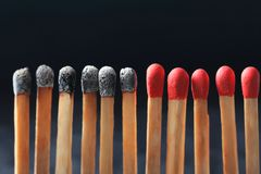Group of burnt matches among others. On black background. Difference and uniqueness concept Royalty Free Stock Photography