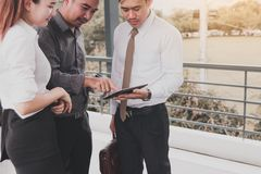 Group of business asian people standing and talking about summary report on tablet screen. stock photos