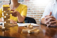 Group of business creative people building tower by wooden block. S, doing a plan for brainstrom business strategy, risk, future, teamwork concept Royalty Free Stock Photography