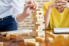 Group of business creative people building tower by wooden block. S, doing a plan for brainstrom business strategy, risk, future, teamwork concept Stock Photos
