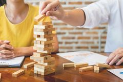 Group of business creative people building tower by wooden block. S, doing a plan for brainstrom business strategy, risk, future, teamwork concept Stock Images