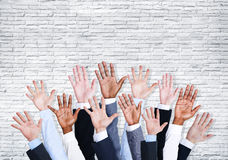 Group of Business Human Arms Raised with Brick Wall Royalty Free Stock Image