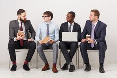 Group of business men sitting on chairs royalty free stock photography