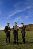 Group of business men watching laptop. Duplicates in the middle of the field inspecting results Royalty Free Stock Image