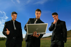 Group of business men watching laptop. Duplicates in the middle of the field inspecting results Stock Image