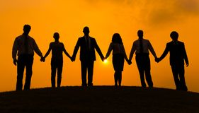 Group of business partner hold hand together in silhouette with sunrise background stock photo
