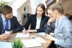 Group of business partners discussing strategies at meeting in office.  stock image