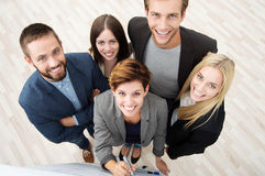 Group of business people from above. Group of five diverse young business people viewed high angle looking up at the camera as they stand at a flipchart having a Stock Images