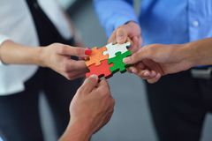 Group of business people assembling jigsaw puzzle. And represent team support and help concept Royalty Free Stock Photography