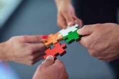 Group of business people assembling jigsaw puzzle Stock Photos
