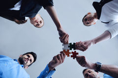 Group of business people assembling jigsaw puzzle Royalty Free Stock Photos