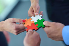 Group of business people assembling jigsaw puzzle Stock Images