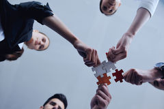 Group of business people assembling jigsaw puzzle Stock Image