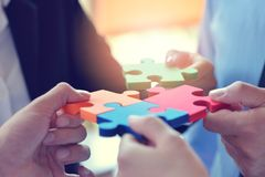 Group of business people assembling jigsaw puzzle and represent. Team support and help concept royalty free stock photo