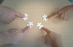 Group of business people assembling jigsaw puzzle wanting to put pieces of puzzle together on wood table backgroung for help suppo Royalty Free Stock Photo