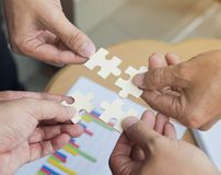 Group of business people assembling jigsaw puzzle wanting to put pieces of puzzle together on wood table backgroung for help suppo royalty free stock photography
