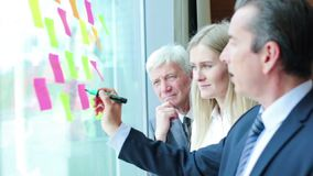 Business people brainstorming ideas. Group of business people brainstorming ideas. Entrepreneurs having a standing meeting discussing ideas strategy planning stock footage