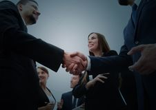 Business handshake. Business handshake and business people conce. Group of business people congratulating their handshaking colleagues after signing contract Royalty Free Stock Images
