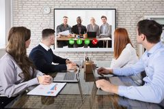 Colleague Doing Video Conferencing In Office. Group Of Business People Doing Video Conferencing In Business Meeting At Office royalty free stock photography