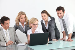 Group of business people in front of a laptop. Smiling business people looking at a laptop computer royalty free stock photos