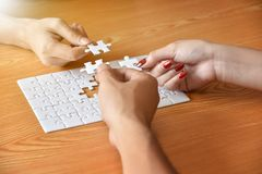 Group of Business people hands are connecting jigsaw puzzle. Group of Business people hands are connecting jigsaw puzzle on desk and solving puzzle together at royalty free stock images