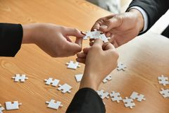 Group of Business people hands are connecting jigsaw puzzle. Group of Business people hands are holding and conecting jigsaw puzzle on desk and solving puzzle Royalty Free Stock Photography