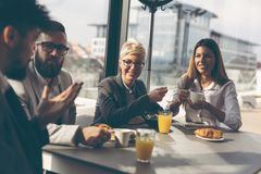 Business people having breakfast. Group of business people having breakfast in company`s restaurant. Focus on the women royalty free stock photography