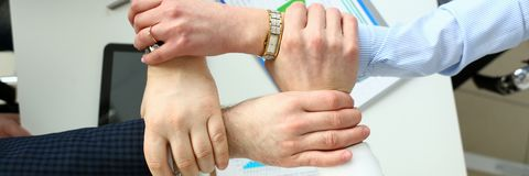 Group business people hold arm in lock. Above office table with chart paper closeup concept stock photography