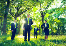 Group of Business People Holding Balloons. In the forest Stock Images