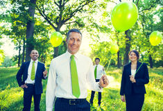 Group of Business People Holding Balloons. In the forest Royalty Free Stock Photo