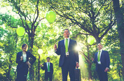 Group of business people holding balloons in the forest.  Royalty Free Stock Image
