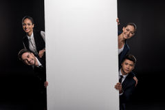 Group of business people holding blank billboard and looking at camera. Isolated on black Royalty Free Stock Photos