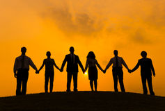 Group of Business People Holding Hand. In Back Lit Stock Photo