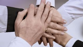 Group of business people holding hands together, symbol of teamwork and support. Stock footage Stock Photos