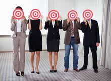 Group of business people holding a target. Against their faces Stock Photo