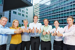 Group of business people holding thumbs up. Successful group of business people holding many thumbs up Royalty Free Stock Photos