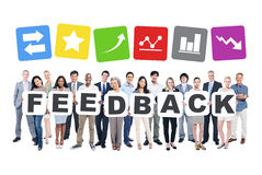 Group Of Business People Holding The Word Feedback. And Related Symbols Above Stock Image
