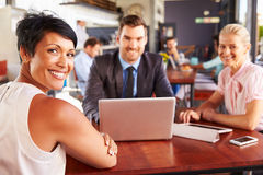 Group of business people with laptop meeting in coffee shop Royalty Free Stock Image