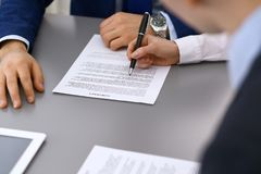 Group of business people and lawyer discussing contract papers sitting at the table, closeup. Businessman is signing. Document after agreement done Stock Photos