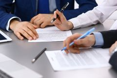 Group of business people and lawyer discussing contract papers sitting at the table, closeup. Businessman is signing. Document after agreement done Royalty Free Stock Images