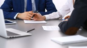Group of business people and lawyer discussing contract papers sitting at the table, closeup. Businessman is signing. Document after agreement done Royalty Free Stock Photos
