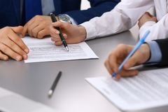 Group of business people and lawyer discussing contract papers sitting at the table, closeup. Businessman is signing. Document after agreement done Stock Image